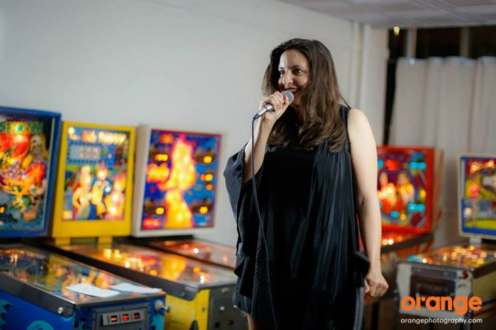 Photo of a woman with long brown hair holding a microphone with pinball machines in the background.