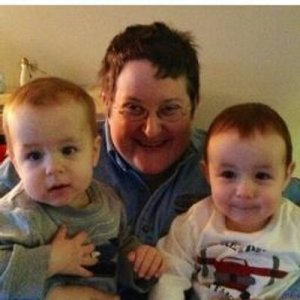 A woman with short hair and glasses holding twin boys who are all smiling at the camera.