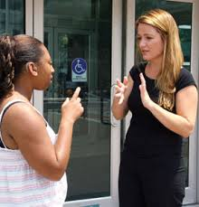 Image of two women using sign language with each other.