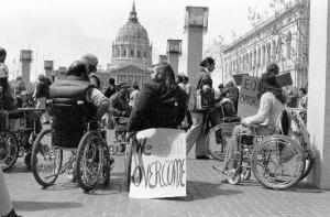 """A black and white image of a group of people protesting in front of San Francisco's City Hall. Many are wheelchair users. One person's wheelchair has a sign that reads: """"We shall overcome."""""""