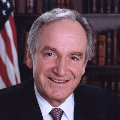 Photo of Senator Tom Harkin. He has short white hair and wearing a dark suit with a white shirt. An American flag and a bookshelf full of books is in the background