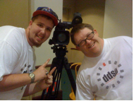 Image of two white men smiling at the camera. One is holding a 'thumbs up' sign. A video camera is between them.