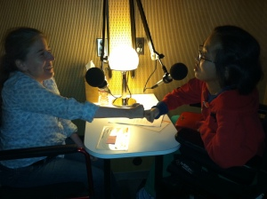 Image of a dim room with two people facing each other, with their fists bumping together. A white woman in a wheelchair is on the left and an Asian-American woman in a wheelchair is on the right.
