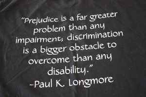 """Dark fabric with a quote printed on it in white: """"Prejudice is a far greater problem than any impairment; discrimination is a bigger obstacle to overcome than any disability."""" --Paul K. Longmore"""