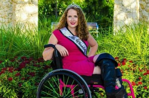 "A young woman in a sleeveless hot pink dress and black leather boots. She is sitting in a wheelchair and wears a crown. She also has a sash that says ""Ms. Wheelchair Florida."""