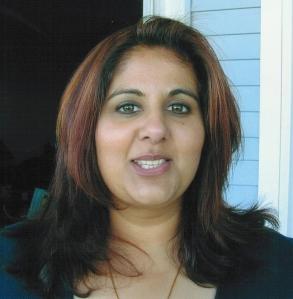 A woman with long dark hair smiling at the camera.