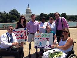 """Photo of 8 people with the Capitol building in the background in Washington, DC. Three people are using wheelchair users. Two people are holding signs that read: """"Nothing about us without us"""" and """"Vote Yes for CRPD."""""""