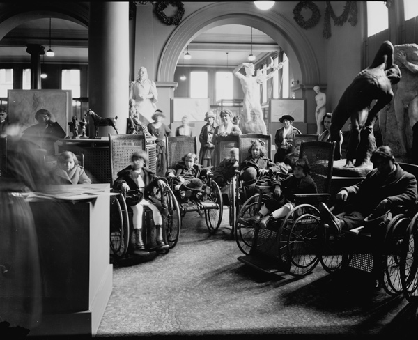 Black and white photo of a group of students in large wheelchairs at the Metropolitan Museum of Art on November 23, 1922