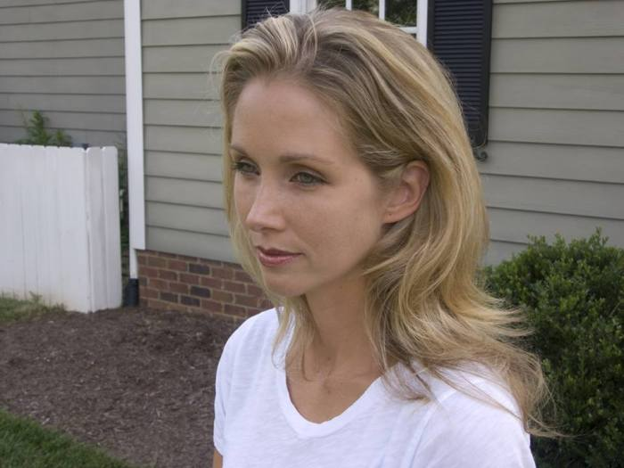 White woman with long blonde hair wearing a white t-shirt. She is staring sideways from the camera.