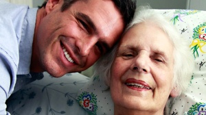 A young man leaning over an older woman who is reclined on a bed. Both are smiling at the camera.