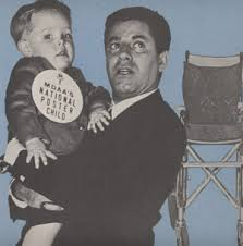 Black and white image of Jerry Lewis holding a toddler boy who has a large button that says he is a Muscular Dystrophy Association poster child. A wheelchair is in the background.