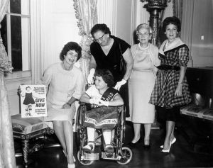 Black and white image of a girl in a wheelchair wearing a sash. She is surrounded by four older white women. A poster of the young girl is featured encouraging people to donate.