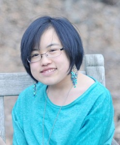 Photo of a young Asian woman with short hair and glasses. She is wearing an aqua blue long-sleeved shirt.