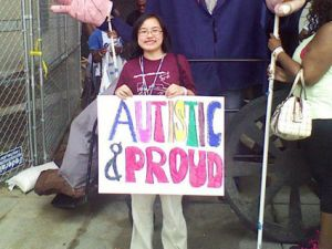 """I am standing in front of several people walking down a stone path, wearing khaki pants and a maroon shirt with the text """"Organizing autistic people..."""" visible while holding a large white poster with the colored block letters """"Autistic & Proud"""" in marker. I am a light-complexioned Asian female with short black hair cut slightly past my chin, wearing round glasses."""