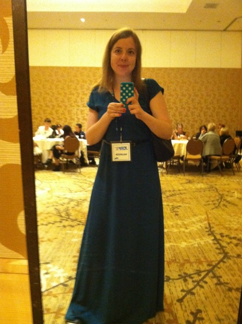 Image of a white woman taking a selfie of herself in front of a mirror. She is wearing a long blue dress and holding her cell phone in front of a mirror.