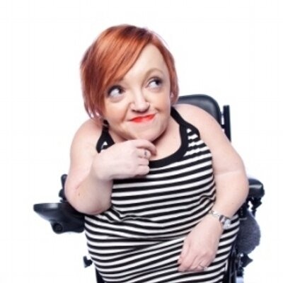 Image of a small white woman with short red hair sitting in a wheelchair. She's looking upward with a smile and her hand touching her chin.