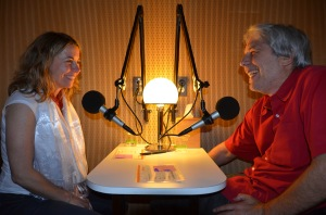 Photo of two people speaking in front of each other a recording booth. On the left is a young white woman with blonde hair and a white shirt. On the right is a white older man in a red shirt using a wheelchair.