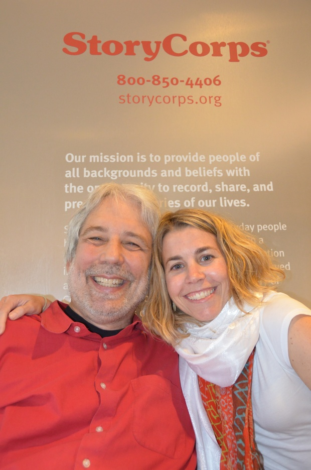 Photo of an older white man in a red shirt and using a wheelchair. He is next to a younger white woman with blonde hair. They are in front of a StoryCorps recording booth.