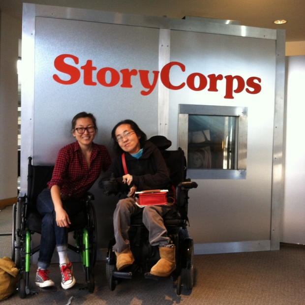 Two Asian American women in wheelchairs sitting in front of a StoryCorps recording booth