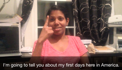"A South Asian woman in a pink shirt using sign language. A caption below the photo reads: ""I'm going to tell you about my first days here in America."""