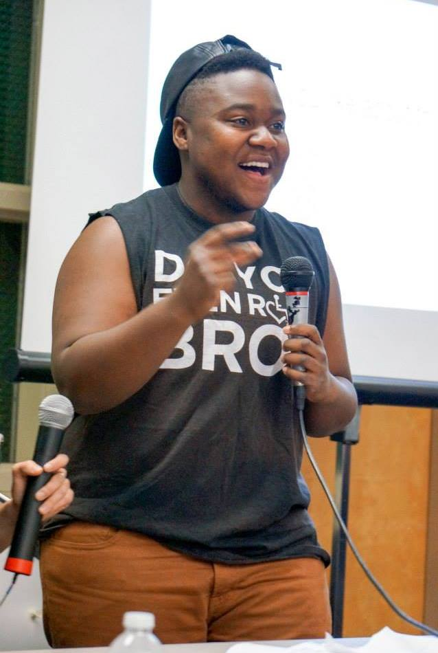 Image description by Ki'tay: A picture of myself wearing a black leather hat that is pointed backwards, a tshirt with the sleeves cut off and brown pants. I am in the midst of talking and am smiling while holding a microphone.