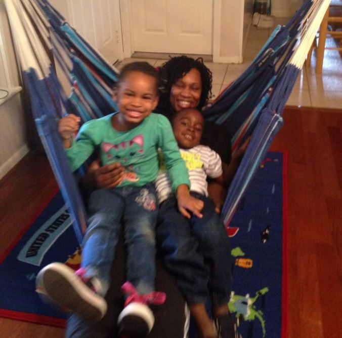 Black woman sitting back in a hammock with two young black boys on her lap. They are all smiling at the camera.