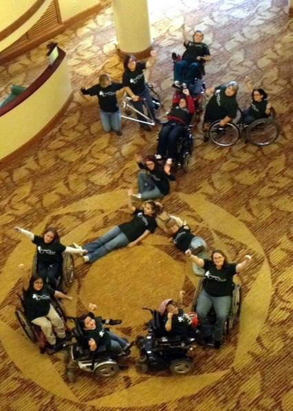 View looking down from a second floor of girls with disabilities, including some in wheelchairs gathered together forming the shape of the symbol for women