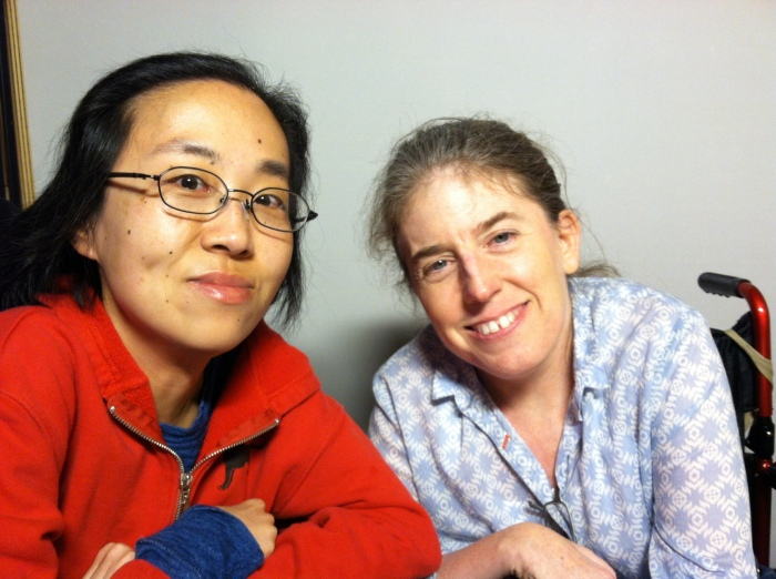 Asian American woman in a wheelchair sitting on the left side. She's wearing a red hoodie and glasses. Next to her is a white middle-aged woman with her hair pulled back and wearing a floral-print shirt. Both are smiling at the camera.