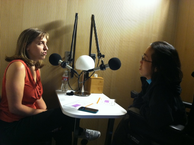 On the left is a white woman with long blonde-brown hair wearing an orange tank top. She is sitting at a table across from an Asian American woman in a wheelchair. She is wearing glasses and wearing a black hoodie. There are microphones on the table and they are having a conversation.