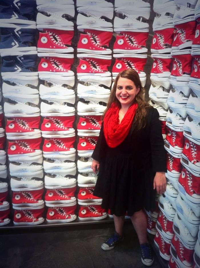Young white woman with long brown hair who is wearing a black dress. She is standing behind a display of rows of sneakers that are red, white and blue.