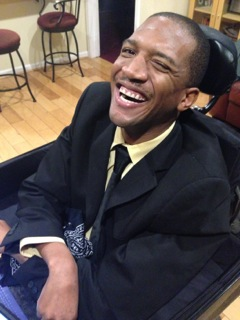 African American man wearing a dark suit and a tie. He's sitting in a wheelchair and smiling at the camera.