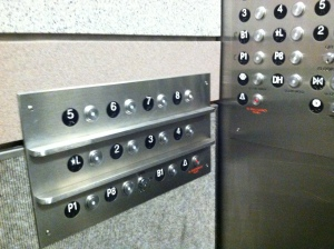 Photo of the inside panel of buttons in an elevator. There are vertical rows of buttons and a set of horizontal buttons on the side of the elevator car.