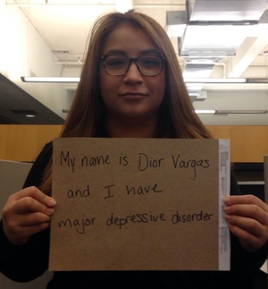 """Photo of a Latina with long brown hair and wearing glasses. She is holding a sign that reads: """"My name is Dior Vargas and I have major depressive order."""""""