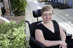 White woman with short blonde hair with glasses. She is wearing a black v-neck top and sitting in a wheelchair outdoor next to some bushes.