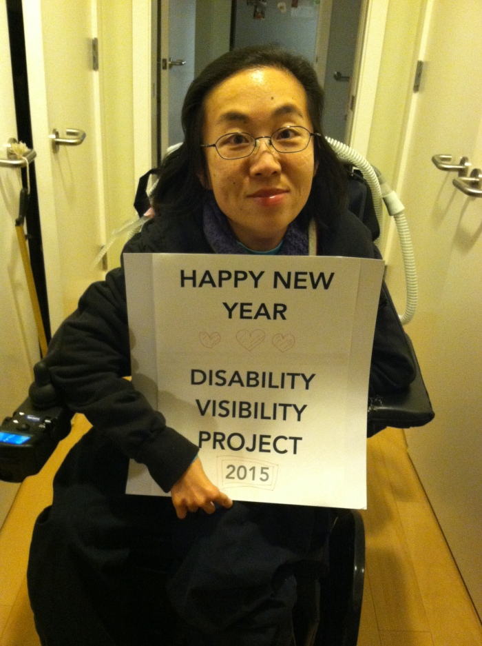 "Image of an Asian-American woman in a wheelchair. She is holding a sign that reads: ""HAPPY NEW YEAR"" below that are 3 hearts and the text: ""Disability Visibility Project 2015"""