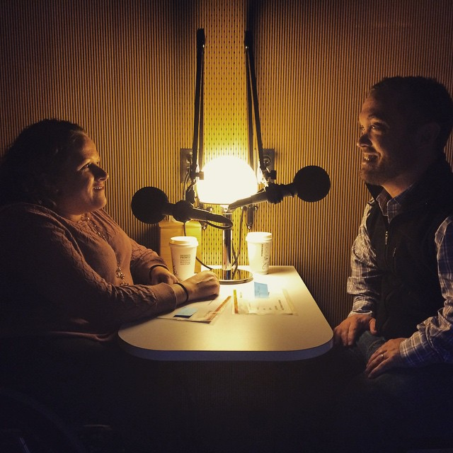 A room with dimmed lighting, two people are sitting across from one another with microphones in front of them. On the left is a middle-aged white woman in a wheelchair with long brown hair. On her right, facing her, is a middle-aged white man with short brown hair.