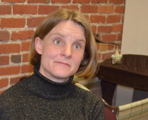 Photo of a white middle-aged woman with shoulder-length blonde hair. She is standing behind a brick wall and is wearing a black turtleneck sweater.