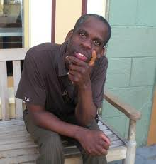 A black man sitting at a wooden bench and one hand is raised, at his chin. He is wearing brown slacks and a brown t-shirt. He is staring right at the camera.
