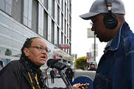 Older African American woman in braids wearing glasses being interviewed by an African American man on the street. He is holding audio equipment and wearing headphones