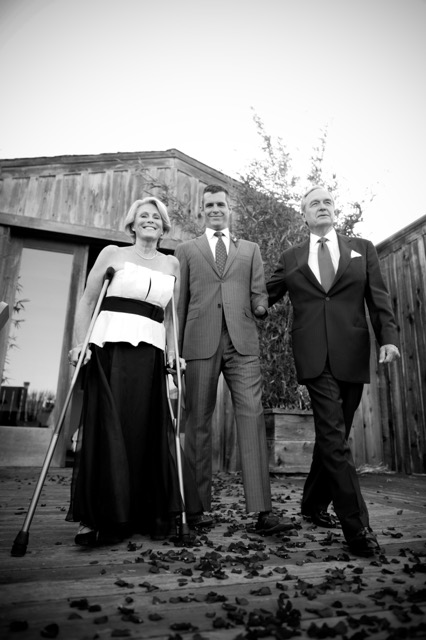 Black and white outdoor image with a barn in the background. A white woman in her 60s is wearing a white and black sleeveless dress. She is using crutches. She is standing left. In the center is a young man, her son dressed in a gray suit. On the right is an older white man in a dark business suit.