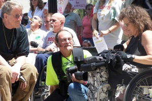 Jack Campbell, a white man in a wheelchair wearing khakis and a black shirt [left], with Tom Olin photographer and historian of the disability rights movement, a white man with a beard and glasses holding a camera and kneeling down [center] and Marilyn Golden, a white woman in a wheelchair with long brown hair of DREDF [right] at DCAD 2007.