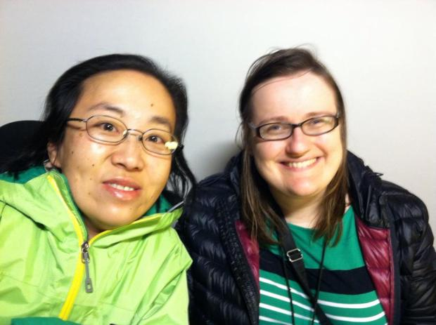 Image of two women sitting side by side. On the left is an Asian woman with glasses and black hair. She is wearing a green jacket. The woman on the right is white and she has long brown hair and glasses. She is wearing a black puffy winter coat and a green sweater.