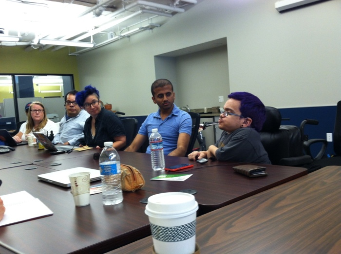 Image of a group of people sitting in a conference room having a conversation on assistive technology