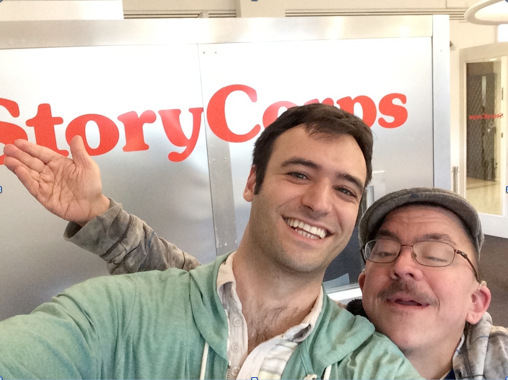 Two men standing in front of a StoryCorps listening booth. The man on the left is younger with brown hair and brown eyes. The man on the right is older with glasses and a mustache. The arms of the second man are outstretched.