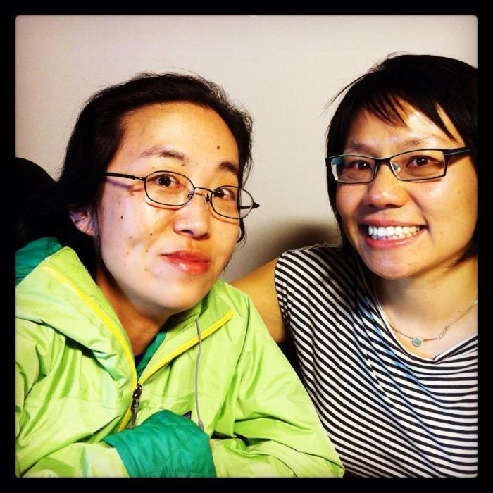 Two Asian American sitting side-by-side. The woman on the left is in a wheelchair; she is wearing a green rain jacket and glasses. The woman on the right has short black hair, glasses and is wearing a striped-t-shirt. They are both smiling at the camera.