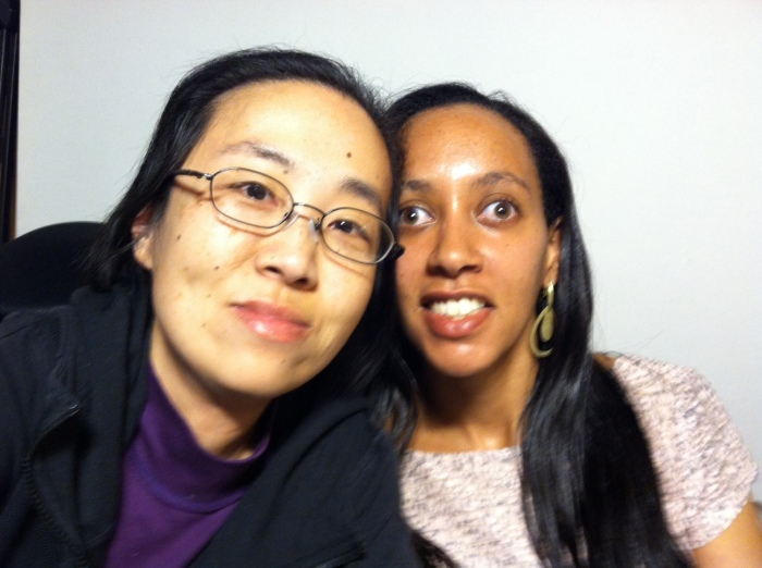 Asian American woman on the left in a black hoodie and wearing glasses. On the right is a young African American woman with long black hair and a short sleeve floral print top