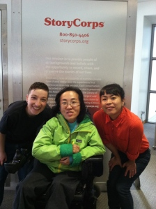 Asian American woman in a wheelchair in the middle of the image on her left and right are two other individuals, staff members of StoryCorps San Francisco. All three are in front of a metal StoryCorps recording booth