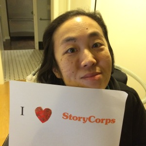 """Image of an Asian American woman in a wheelchair holding a paper sign that reads, """"I [heart symbol] StoryCorps"""""""