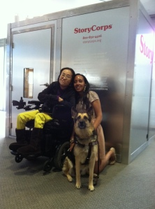 An Asian American woman in a wheelchair next to a young African American woman who knelt down to the same height as the wheelchair user. Between these two people is Maxine, a German shepherd service animal. The three of them are in front of a StoryCorps recording booth.