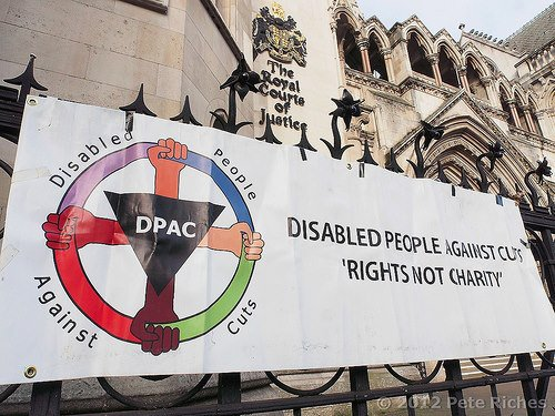 "Banner outside of the Royal Court of Justice in the United Kingdom. The banner has a circular logo with 4 fists positioned in the north, west, east, south position. The text reads: DPAC Disabled People Against Cuts. ""Rights, Not Charity."""